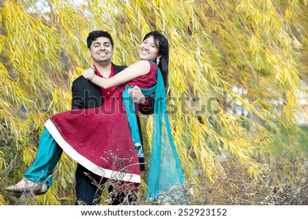A happy young indian man carrying his fiancee near a willow tree on a sunny day in the fall. - stock photo