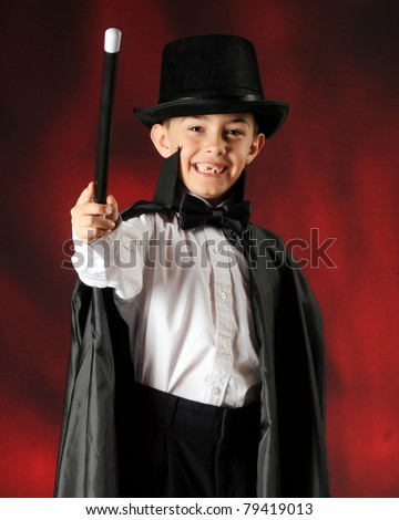 A happy young magician waving his want at the viewer. - stock photo