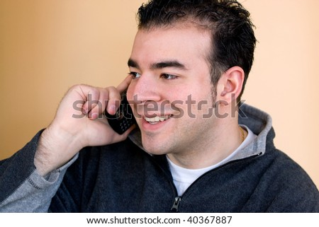 A happy young man having a conversation on his cell phone. - stock photo