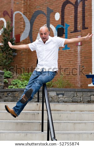 A happy young man sliding down a railing on a stairway. - stock photo
