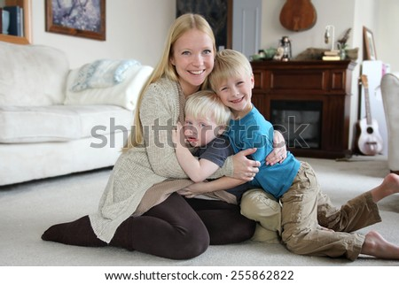 A happy young mother is hugging her two young children as they sit on the carpet in their living room. - stock photo