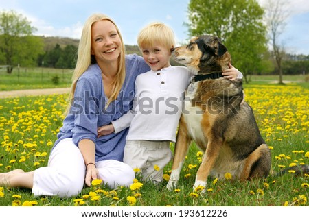 A happy young mother is sitting in a meadow of Dandelion Flowers with her little Child and her German Shepherd dog. - stock photo