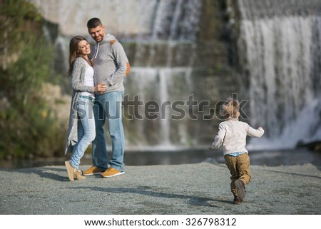 A happy young parents and their son on a waterfall background