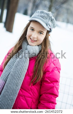 A happy young teenager dressed for winter in the snow in central park New York - stock photo