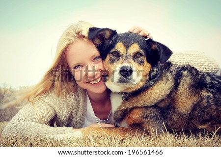 a happy young woman and her German Shepherd dog are laying on the grass outside hugging. Vintage style color. - stock photo