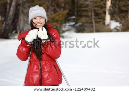 A happy young woman in red in the snow - stock photo