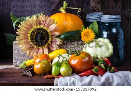 A harvest table full of freshly harvested vegetables and flowers. - stock photo