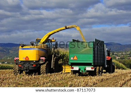 A harvester cuts a field of maize for silage in Switzerland. Space for text in the sky.