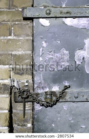 A hasp and staple on an old warehouse door.