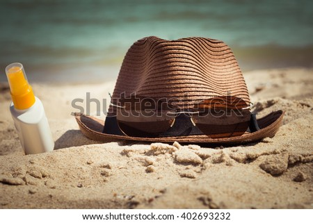 A hat with sunglasses and a bottle of sunscreen lotion lying on the sand. Vacation theme. Toned effect - stock photo