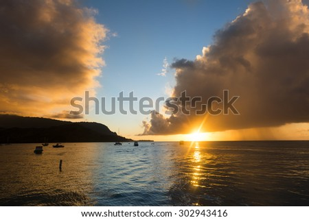 A Hawaiian sunset just after a storm shows the dark clouds still lingering over the calm Hanalei Bay. - stock photo