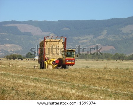 A hay stacker flanked by mountains. - stock photo