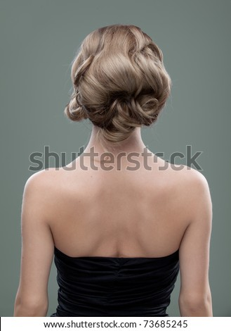 a head and shoulders image of a young woman, from the back. her hair is long and blonde and she is showing an interesting, wavy hairstyle. - stock photo