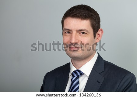 A head and shoulders shot of a 40 year old business man in a suit and shirt with blue tie. - stock photo