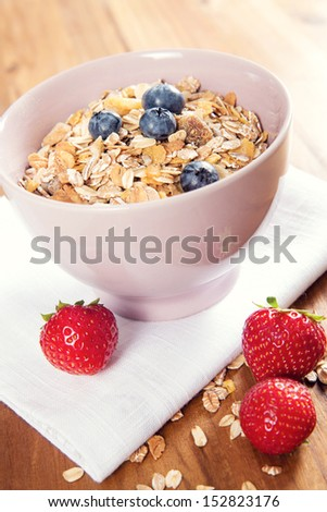 A healthy bowl of muesli with fresh berries on the table.