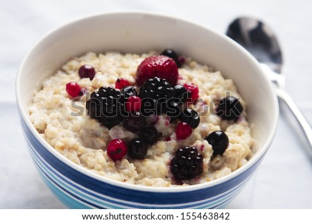 A healthy bowl of porridge served with fresh berries - stock photo