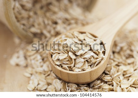 A Healthy Dry Oat meal in a wooden spoon - stock photo