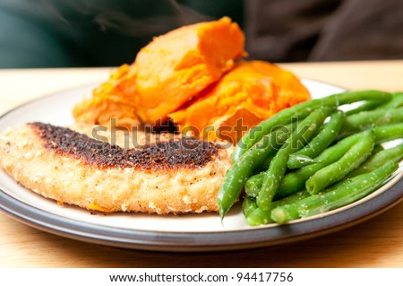 a healthy meal including breaded and fried tilapia fish fillet with sweet potatoes and green beans. - stock photo