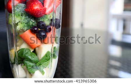 a healthy mix of vegetables and fruit in a mixer sitting on a wooden deck - stock photo