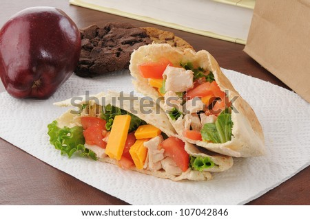 a healthy school or sack lunch with a chicken pita sandwich, apple and cookies - stock photo