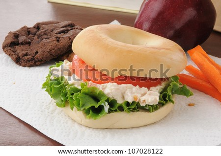 A healthy school sack lunch with a chicken salad pita sandwich with carrot sticks, cookies and an apple - stock photo