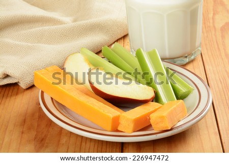 A healthy snack with celery sticks, apple slices and cheese - stock photo