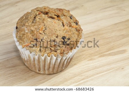 A healthy whole grain carrot raisin muffin with bran on a wooden surface. - stock photo