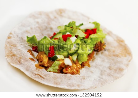 A healthy whole grain fajita based on whole grain with chicken fillet, onion, cucumber and salad.