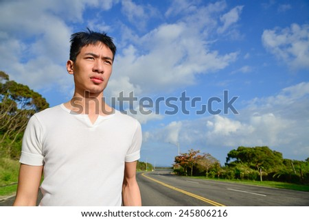 A healthy young man standing in the tree pose outdoors - stock photo