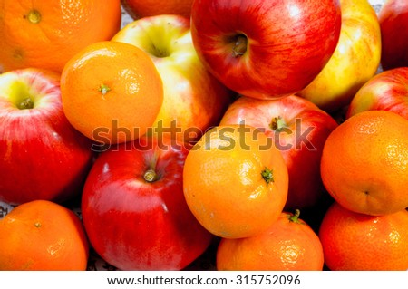 A heap of apples, oranges and tangerines on a flowery fabric, under the sunlight - stock photo