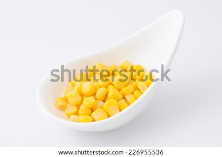 a heap of canned corn on a plate on white background - stock photo