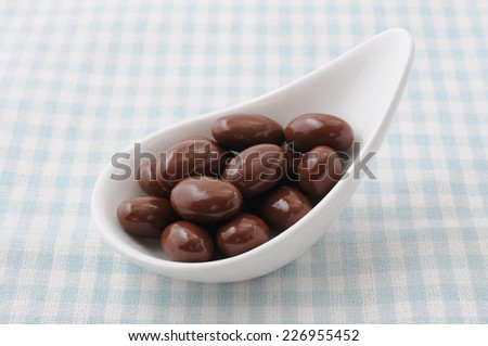a heap of chocolate covered almonds on a plate on tablecloth - stock photo