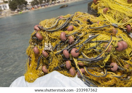 a heap of fishing net on the dock of a port with beach on background - stock photo