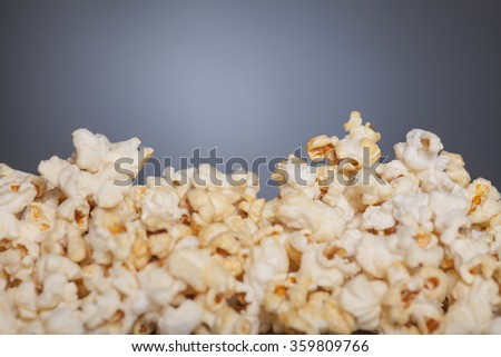 A heap of popcorn on front of grey background with vignette and copyspace on top.