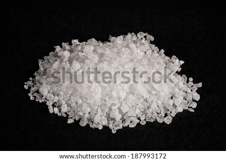 A heap of sea salt on black background - stock photo