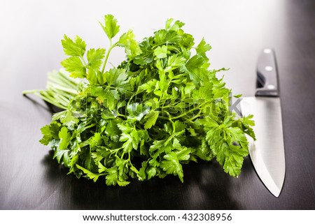 a heap of vibrant green parsley and a kitchen knife on a dark wooden surface - stock photo