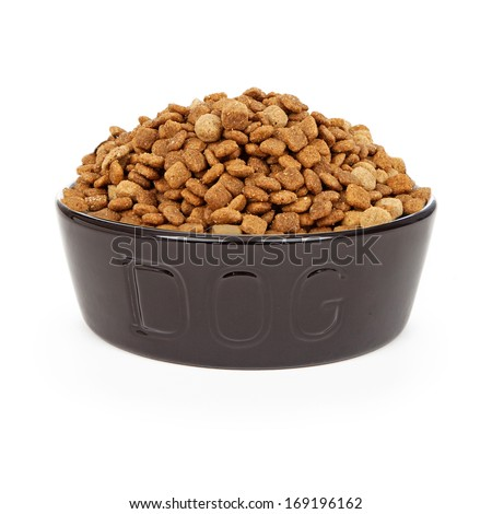A heaping bowl of dry kibble dog food in a black bowl with the letters DOG on it. Isolated against a white background.