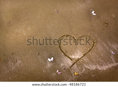 A heart drawn in the sand with colorful little butterfly shells.