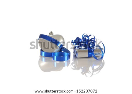A heart in silver and a beautiful package with blue ribbon reflected in a white background
