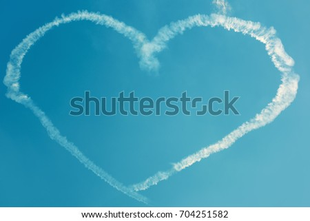 A heart in the blue sky from skywriting planes at an air show