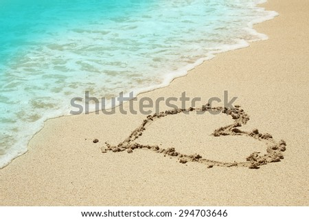 a heart in the sand on the beach - stock photo