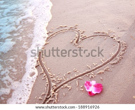 a heart in the sand on the seashore  - stock photo