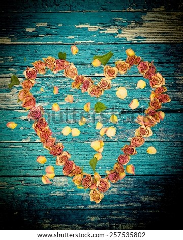 a heart made with old dried up flowers on a piece of weathered wood with cracked paint - stock photo