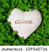 A heart of stone with good wishes, lying between lucky clover - stock photo