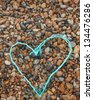 A heart shape made out of fishing rope on a colourful pebble beach - stock photo