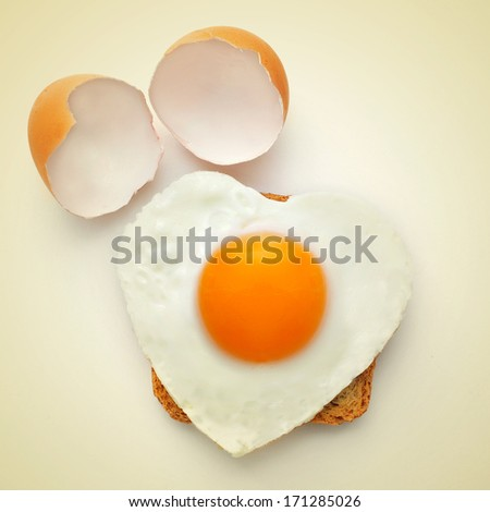 a heart-shaped fried egg on a toast and the cracked shell on a beige background, with a retro effect - stock photo