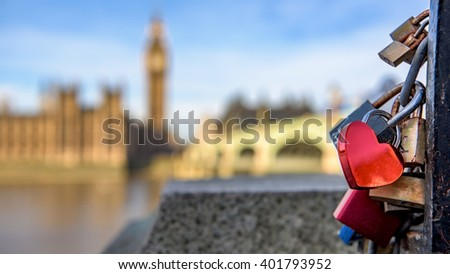 A heart shaped lock connected to other locks near Westminster bridge, Big Ben defocused in the background. - stock photo