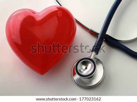 A heart with a stethoscope, isolated on wooden background - stock photo