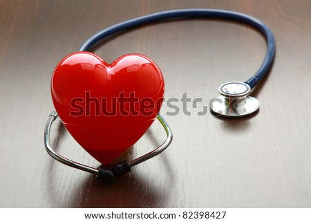 A heart with a stethoscope lying on a wooden desk - stock photo