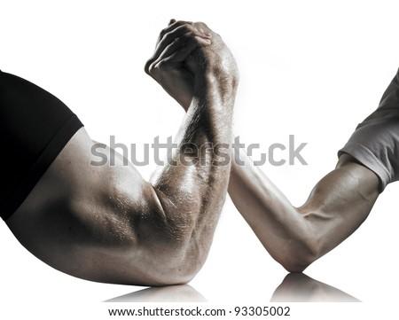 A heavily muscled man arm wrestling a puny weak man - stock photo
